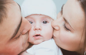 A baby being kissed by parents in family portrait