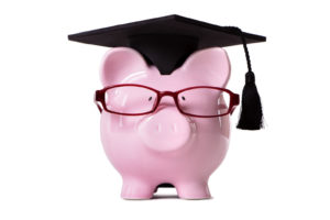 Piggy bank in graduation cap and glasses
